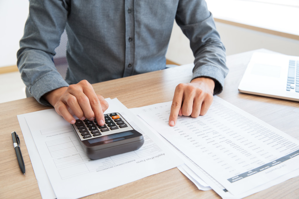 Close-up of unrecognizable man working with financial data. He using calculator and examining document. Financial inspector holding examination. Paperwork or finance concept